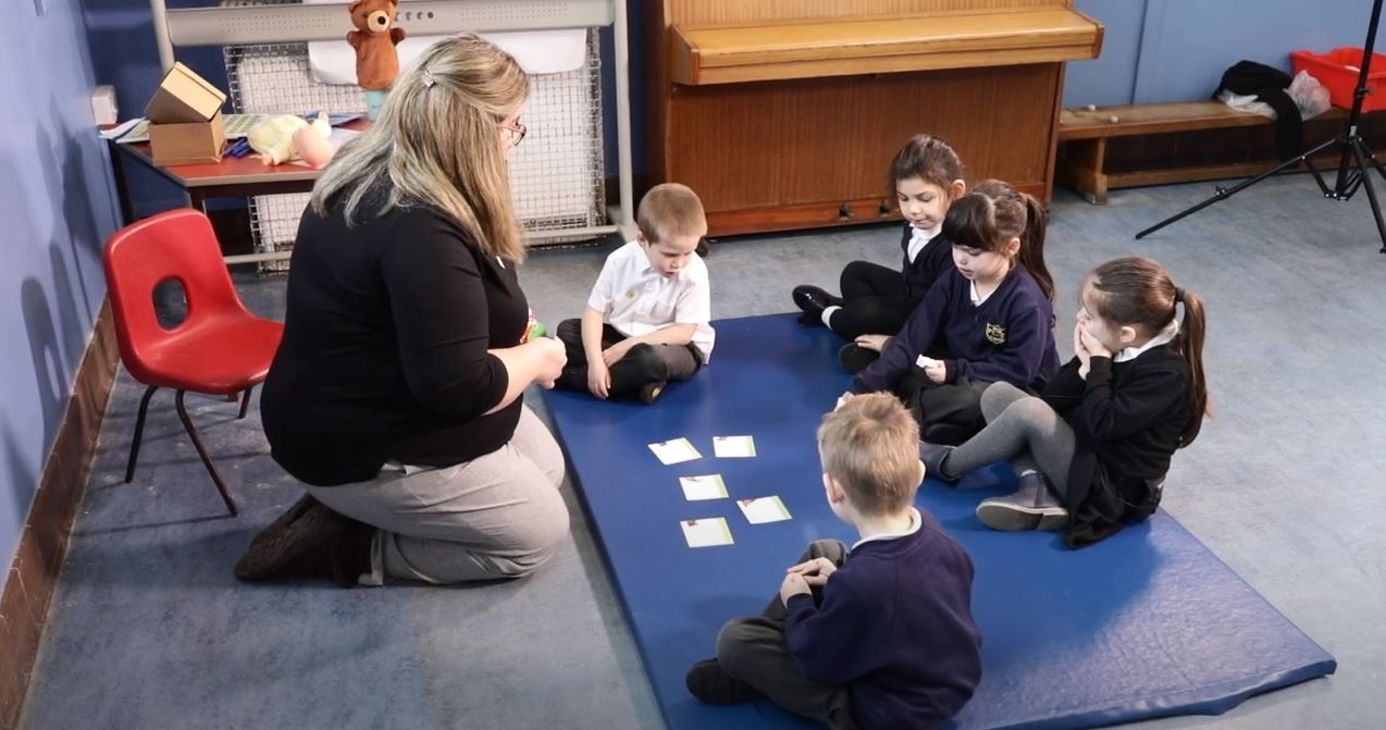 Teaching assistant and children in a group NELI session